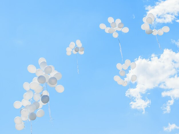 Białe balony jak chmury latają wysoko w niebo.