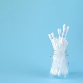 Białe bawełniane waciki lub patyczki do higieny osobistej w szklanym słoju