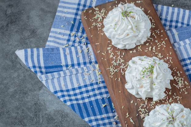Białe bezowe ciasteczka na drewnianej desce z pudrem kokosowym na wierzchu.