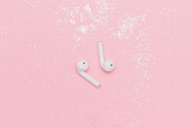 Białe bezprzewodowe słuchawki bluetooth i brokat konfetti na różowym tle papieru.