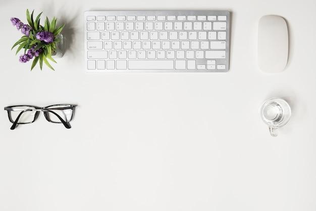 Białe biurko biurowe z gadżetami komputerowymi i dostawami.