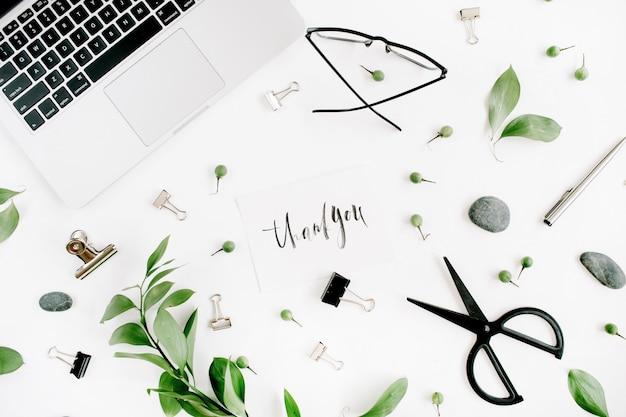 Białe biurko obszar roboczy z pustymi i zielonymi liśćmi