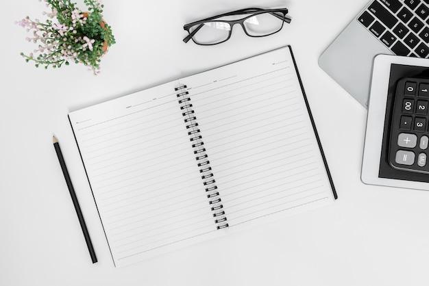 Białe biurko. stół z pustym notatnikiem, tabletem, kalkulatorem, komputerem i innymi artykułami biurowymi