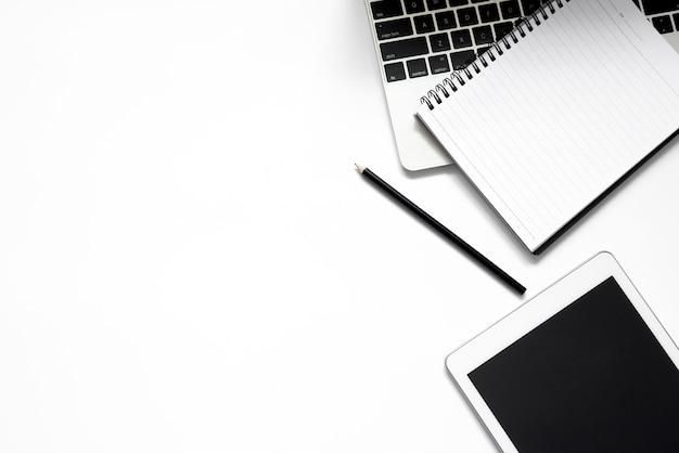 Białe biurko. stół z pustym notatnikiem, tabletem, okularami, kalkulatorem, komputerem i innymi artykułami biurowymi. widok z góry z miejscem na kopię.