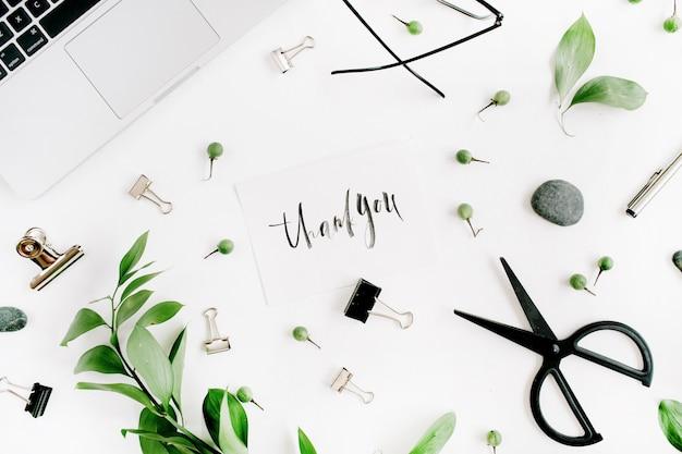 Białe biurko z cytatem dziękuję, zielone liście i materiały biurowe