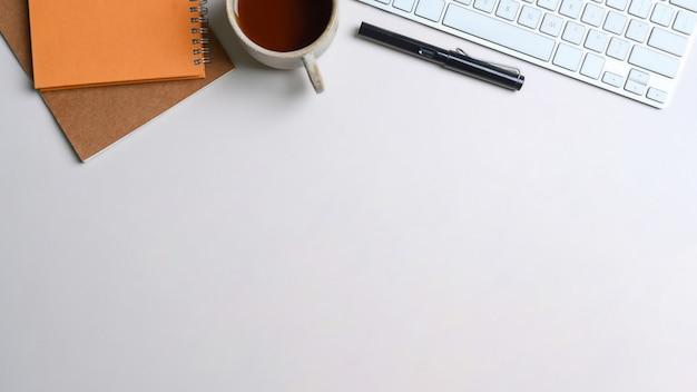 Białe biurko z klawiaturą, notatnikiem, filiżanką kawy i długopisem.
