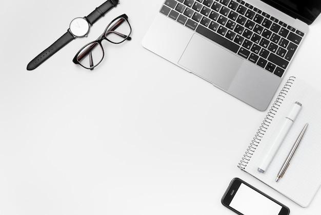 Białe biurko z laptopem i materiałami eksploatacyjnymi. widok z góry okulary, zegarek, telefon, długopis, marker i notatnik z bezpłatną przestrzenią, płaskie świeckich tło.