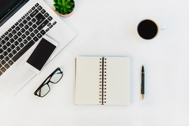 Białe biurko z laptopem, smartfonem i innymi materiałami do pracy z filiżanką kawy. widok z góry, miejsce, płaski układ.