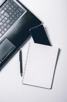 Białe biurko z laptopem, smartfonem i pustą stroną zeszytu. widok z góry