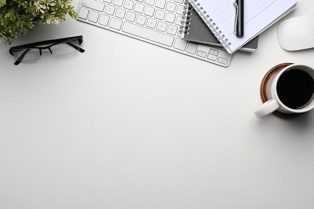 Białe biurko z notatnikiem, bezprzewodową klawiaturą, filiżanką kawy, okularami i miejscem na kopię.