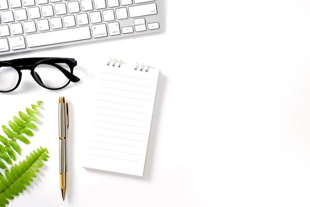 Białe biurko z notatnikiem komputerowym długopis zielony liść i inne materiały