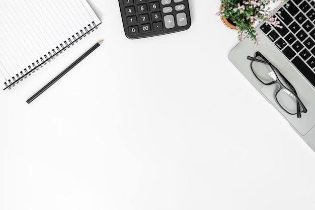 Białe biurko z pustym notatnikiem, okularami, kalkulatorem, komputerem i innymi artykułami biurowymi