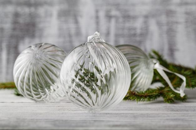 Białe bombki i gałęzie sosnowe leżą w śniegu (nastrój świąteczny)