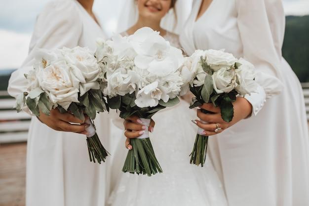 Białe bukiety ślubne dla panny młodej i druhen wykonane z kalii i storczyków w rękach na zewnątrz