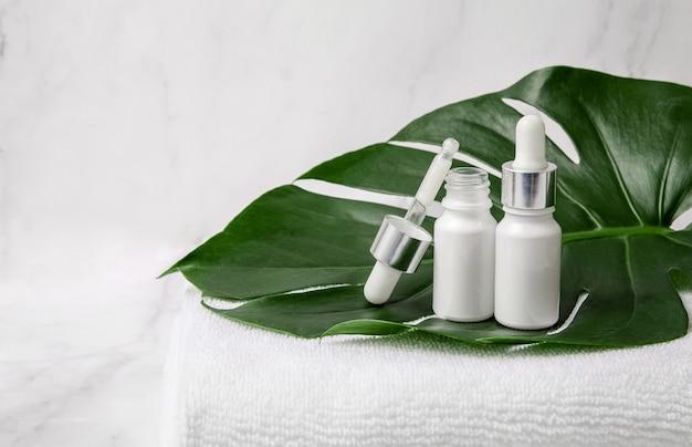 Białe butelki kosmetyczne i zakraplacz z ręcznikiem i zielonym liściem na marmurowym tle.