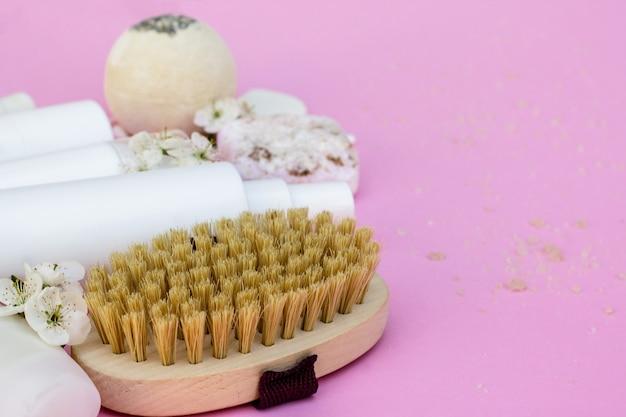 Białe butelki kosmetyczne, kula do kąpieli, ręcznie robione mydło, sól do kąpieli, szczoteczka do masażu, gąbka, patyczki kosmetyczne z kwiatami wiśni na różowym tle. koncepcja naturalnych kosmetyków organicznych.