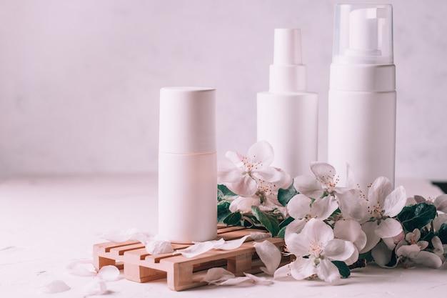 Białe butelki z kosmetykami na drewnianym podium w formie palety na jasnej tynkowej powierzchni z kwiatami jabłoni. skopiuj miejsce