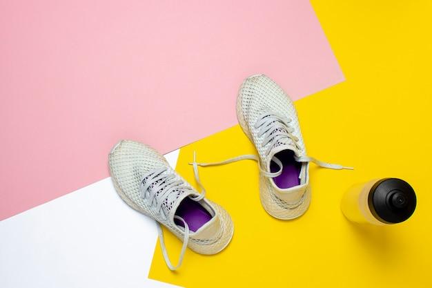 Białe buty do biegania i bidon na abstrakcyjnej kolorowej powierzchni. pojęcie biegania, treningu, sportu. . leżał płasko, widok z góry