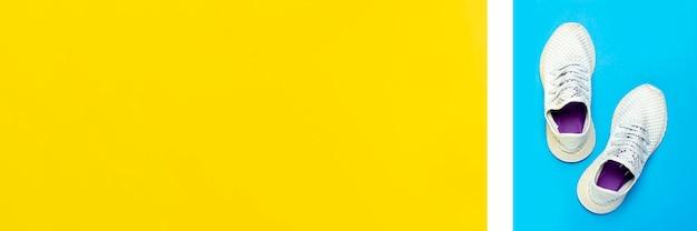 Białe buty do biegania na abstrakcyjnej powierzchni żółtej i niebieskiej. pojęcie biegania, treningu, sportu. . leżał płasko, widok z góry