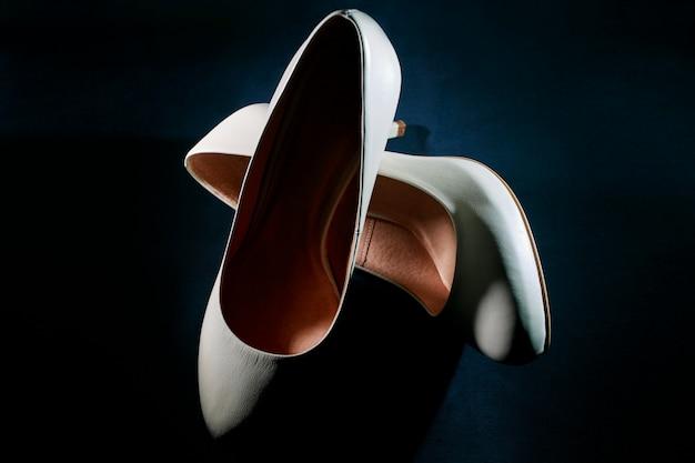 Białe buty ślubne na ciemnym bliska. białe skórzane damskie buty na obcasie na czarnym tle. para klasycznych butów damskich. akcesoria ślubne