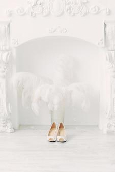 Białe buty ślubne nad kominkiem i strusie pióra w białym wnętrzu
