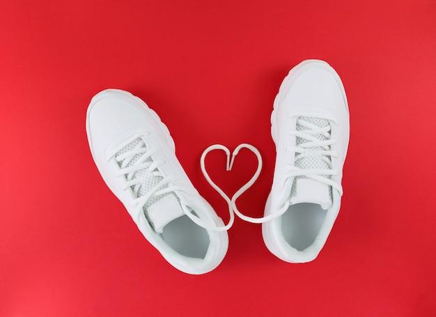 Białe buty sportowe i serce ze sznurowadeł na czerwonej podłodze. prosty płaski układ.
