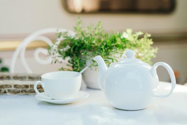 Białe ceramiczne czajniki i składniki herbaty, biały stół z doniczką.