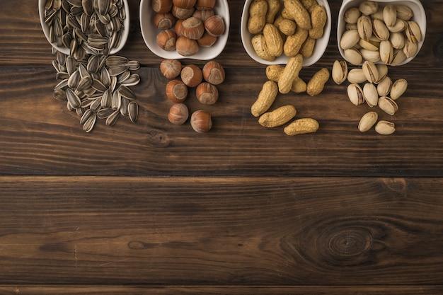 Białe ceramiczne filiżanki z rozlanymi orzechami i nasionami. mieszanka orzechów i nasion.