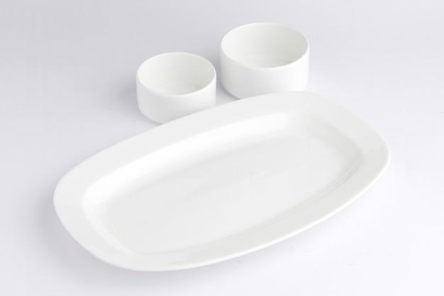 Białe ceramiczne naczynia stołowe ułożone na białym tle