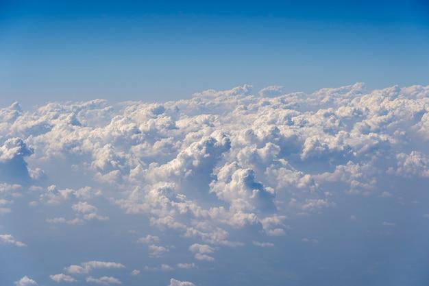 Białe chmury i błękitne niebo, widok z okna samolotu. tło natury