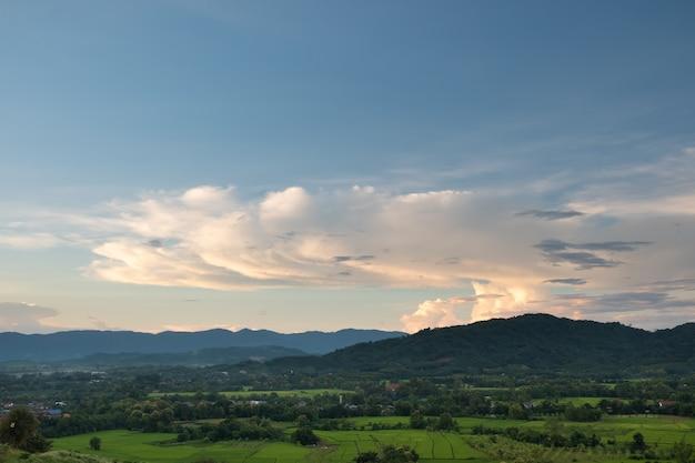 Białe chmury mają dziwny kształt i górę, niebo i otwarta przestrzeń mają góry poniżej, chmury unoszące się nad górami.