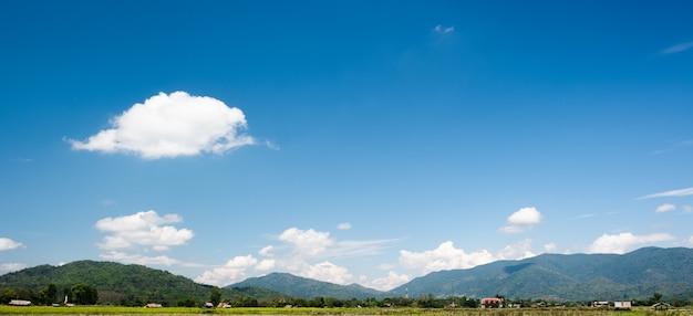 Białe chmury mają dziwny kształt i wiejską okolicę. pochmurno i błękitne niebo.