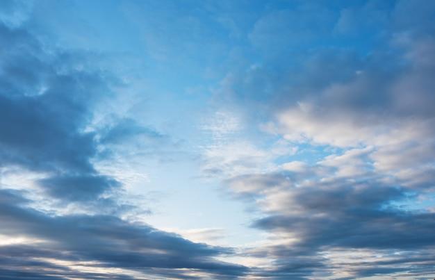 Białe chmury pierzaste, pierzaste chmury na tle błękitnego nieba o zachodzie słońca