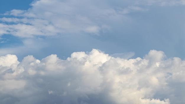 Białe chmury ustawiły się w rzędzie na niebieskim niebie