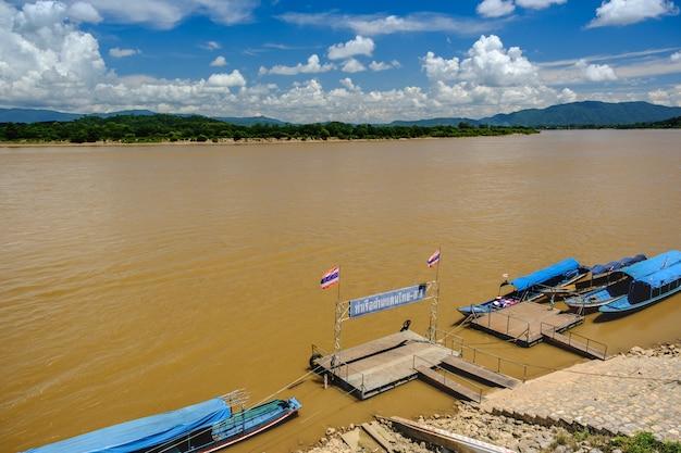 Białe chmury z niebieskim niebem, długi ogon łodzi zacumowanej przy rzece mekhong