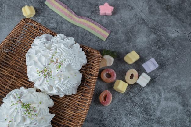 Białe ciasteczka bezowe na drewnianym talerzu z żelkami dookoła.