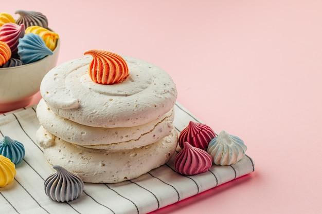Białe ciasteczka bezowe na różowym tle z kolorowymi mini bezy z bliska