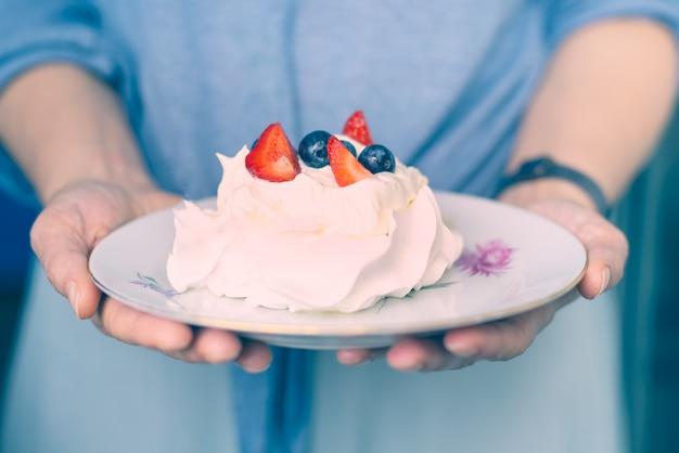 Białe ciasto, beza z owocami i jagodami w rękach kobiety
