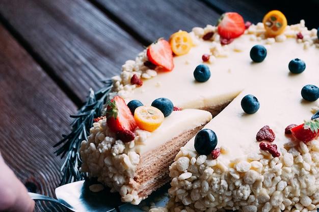 Białe ciasto czekoladowe z jagodami, całe z krojonym plasterkiem