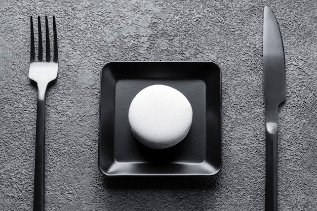 Białe ciasto makaronowe w czarnym kwadratowym talerzu. piękna kompozycja, minimalizm.