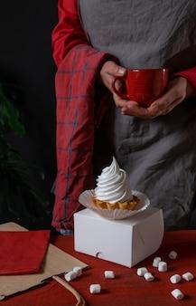 Białe ciasto na białym pudełku dostawy papieru i cukiernik z czerwoną filiżanką kawy w dłoniach