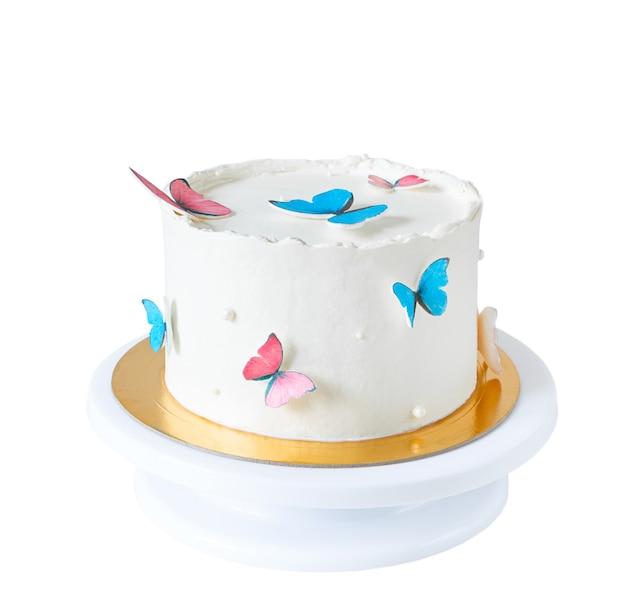 Białe ciasto ozdobione niebieskimi i różowymi motylami na białym tle