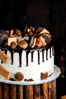 Białe ciasto polane czekoladą i ozdobione ciasteczkami oreo i tofifi
