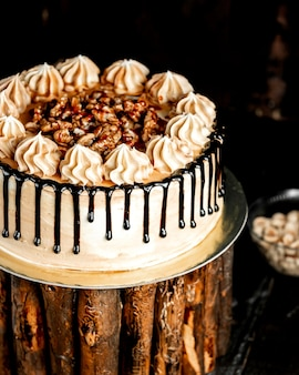 Białe ciasto polane czekoladą i ozdobione orzechami