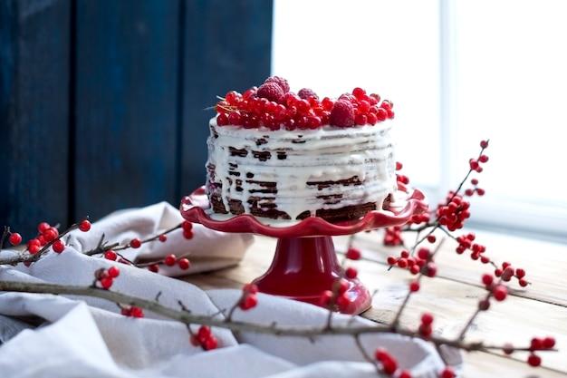 Białe ciasto z czerwonymi jagodami i gałąź na stole w pobliżu okna