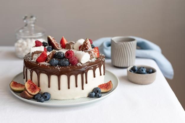 Białe ciasto z różnymi jagodami i czekoladą na lnianym obrusie koncepcja urodzinowego dnia matki