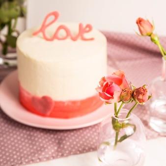 Białe ciasto z różowym wystrojem i słowo miłość na górze wśród małych białych i różowych róż. koncepcja prezent walentynki