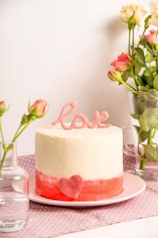 Białe ciasto z różowym wystrojem i słowo miłość na górze wśród małych białych i różowych róż