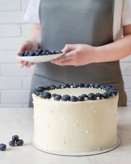 Białe ciasto z twarogiem i świeżymi jagodami. cukiernik dekorowanie ciasta jagodami.