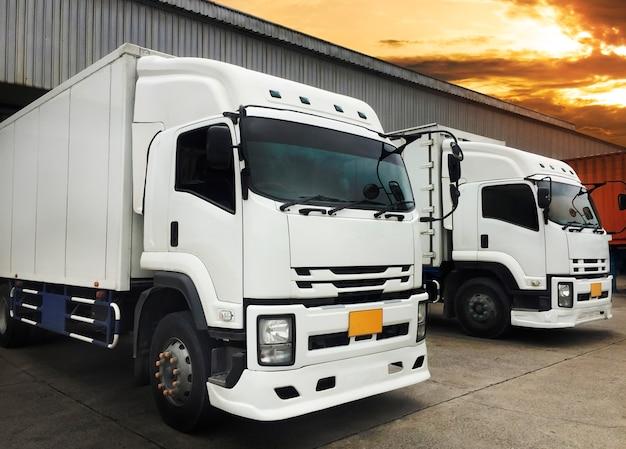 Białe ciężarówki dokują ładunek w magazynie, logistyka transportu towarowego